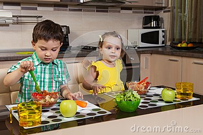 Two children who eat healthy food in the kitchen