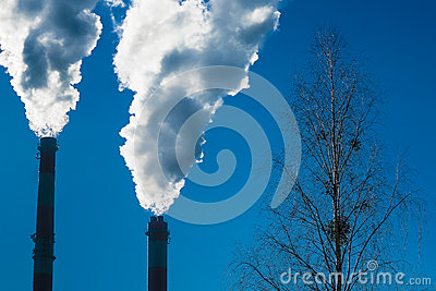 Two chimneys with dramatic clouds of smoke.