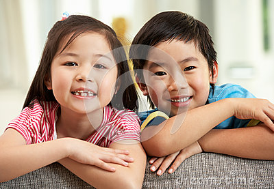 Two  Chinese Children Relaxing On Sofa At Home