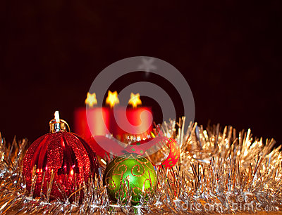 Two Christmas ornaments with candles on the backgr