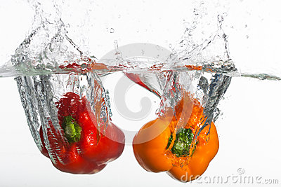 Two clear peppers is thrown into clean water.