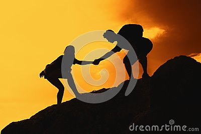 Two climbing people in mountains as symbol for help and success Stock Photo