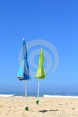 Two closed parasols on the beach