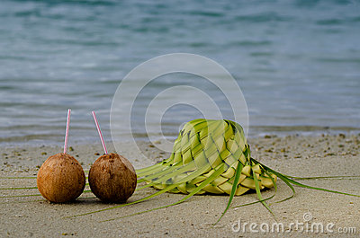 Two coconuts and sun hat on the sandy sea shore