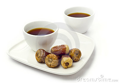 Two coffee cups and dates.