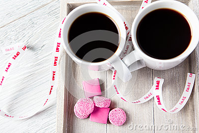 Two coffee cups with pink candies