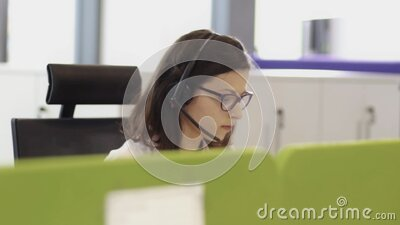 Two colleagues wearing headsets working in a call center stock footage