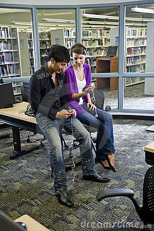 Two college students with music players in library