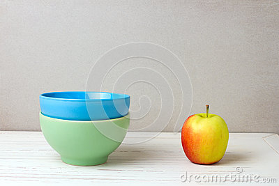 Two colorful bowls and apple