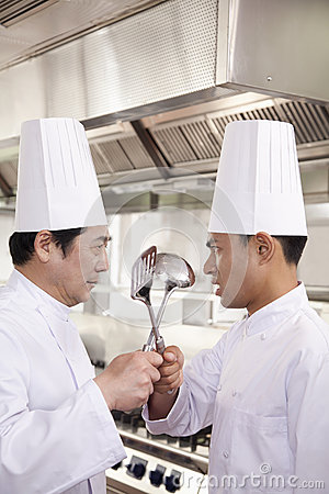 Two Competitive Chefs Face Off with Kitchen Utensils in Hands
