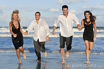 Two Couples, Having Fun Running At The Beach