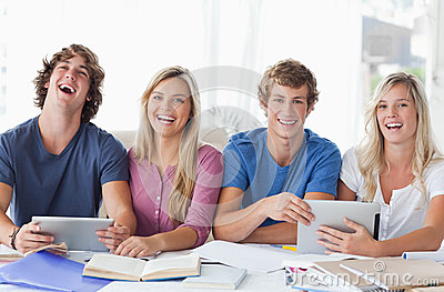 Two couples sit together and work with the help of tablet pc s
