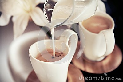 Two cups of coffee with decoration and poured milk