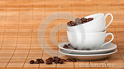 Two cups at each other with coffee grains on the sauce