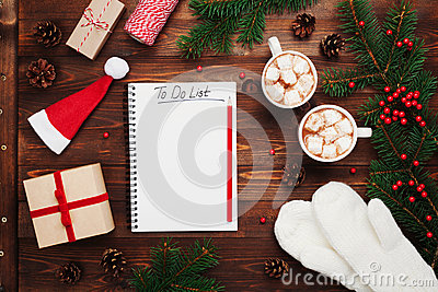 Two cups of hot cocoa or chocolate with marshmallow, gifts, mittens, christmas fir tree and notebook with to do list. Flat lay. Stock Photo