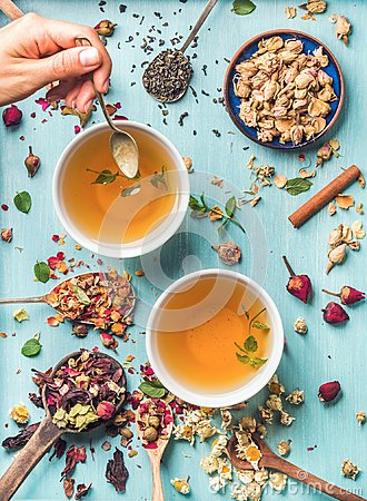 Free Two Cups Of Healthy Herbal Tea With Mint, Cinnamon, Dried Rose, Camomile Flowers In Spoons And Man`s Hand Holding Spoon Stock Images - 103908594