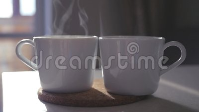 Two cups of steaming coffee stand on the table. Slowmotion. 1920x1080. Two cups of steaming coffee stand on the table, slowmotion stock video footage