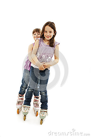 Two cute girls holding hands wearing roller skates
