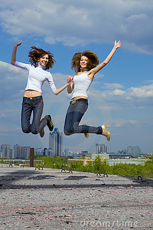 Two cute girls jumping and having fun