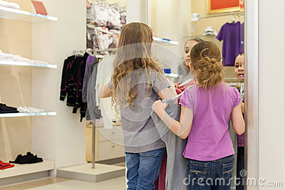 Two cute girls near a mirror try on clothes in a modern store