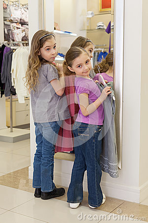 Two cute girls near a mirror try on clothes in a store