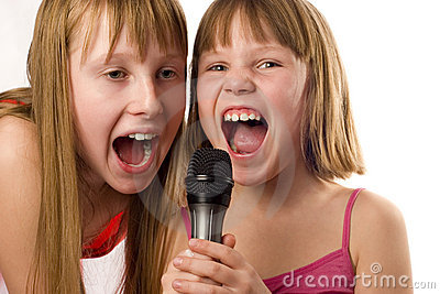 Two cute girls singing to microphone