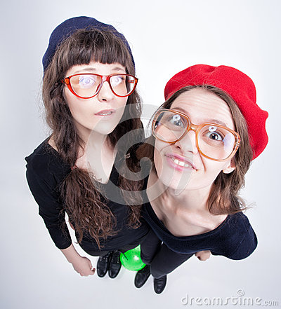 Two cute girls wearing granny s glasses making funny faces