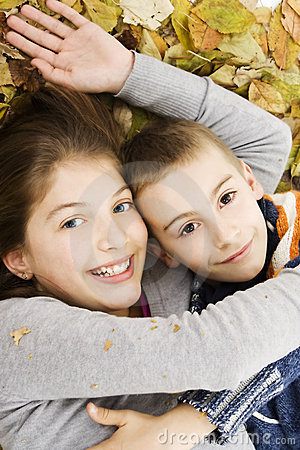 Two cute kids lying down with leaves around