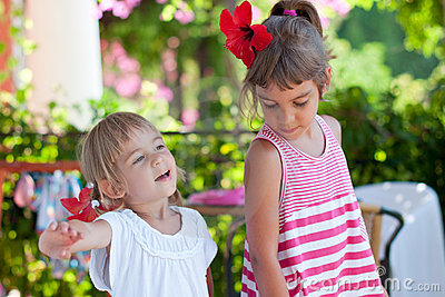 Two cute little sisters summer outdoor portrait