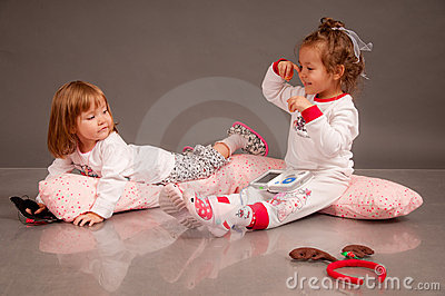 Two cute little sisters in white pajamas