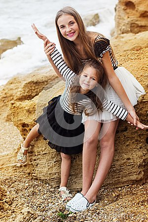 Free Two Cute Sisters Are Standing On The Beach Stock Photography - 56346792