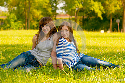 Two cute smiling teenage girls sitting on the gras