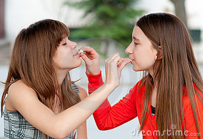 Two cute teenage girls feeding each other