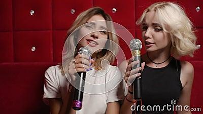 Cute young girlfriends sing karaoke on a red quilted background. Two cute young girlfriends sing karaoke on a red quilted background stock footage