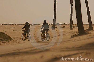 Two cyclists cycling in a desert braving sand and wind