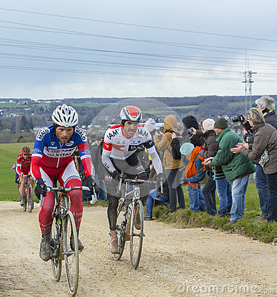 Two Cyclists on a Dirty Road - Paris-Nice 2016 Editorial Photo