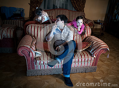 Two daughters disturbing father while watching TV at night