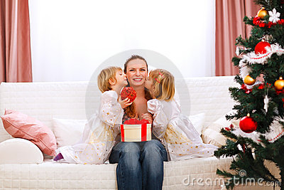 Two daughters kissing mother near Christmas tree