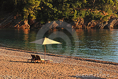 Two deck chairs and umbrella on the beach.