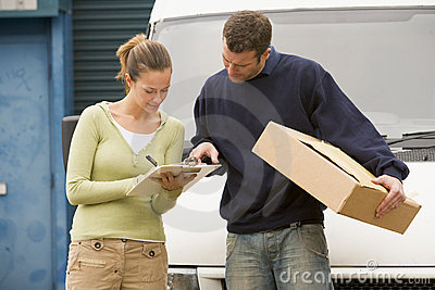 Two delivery people standing infront of van