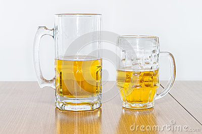 Two Different Beer Mugs Half Full with Lager