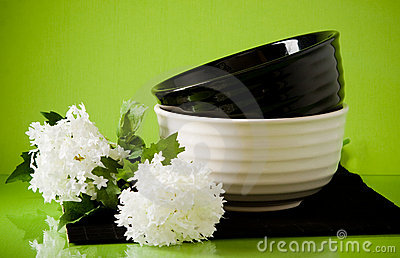 Two dishes with spring flowers on green