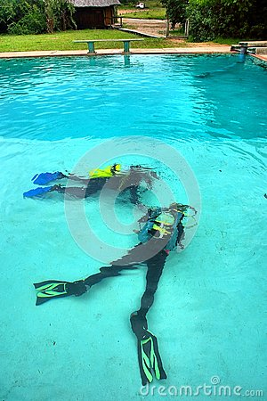 Two divers lie on bottom