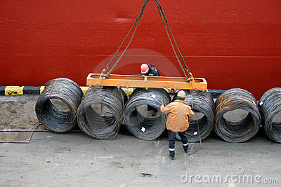 Two dockers fix a cargo of a wire for loading
