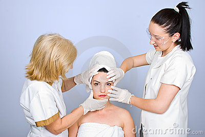 Two doctor holding hands on  woman face
