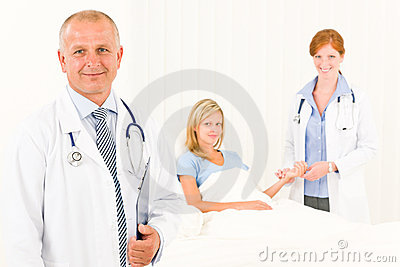 Two doctors with patient lying in bed