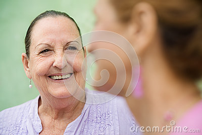 Two elderly women talking on park bench