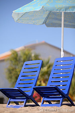 Two empty chairs stand under beach umbrella