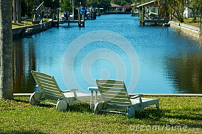 Two empty chairs by the water