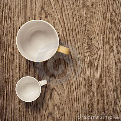 Two empty cups on wooden floor